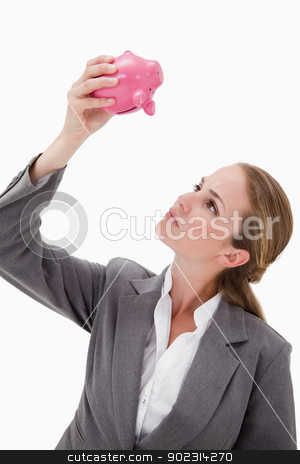 Bank employee looking at piggy bank stock photo, Bank employee looking at piggy bank against a white background by Wavebreak Media