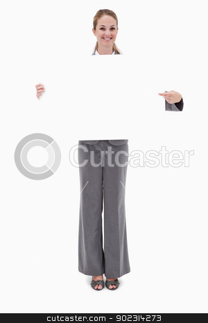 Smiling bank employee holding and pointing at blank sign stock photo, Smiling bank employee holding and pointing at blank sign against a white background by Wavebreak Media