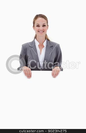 Smiling bank employee holding blank sign in her hands stock photo, Smiling bank employee holding blank sign in her hands against a white background by Wavebreak Media
