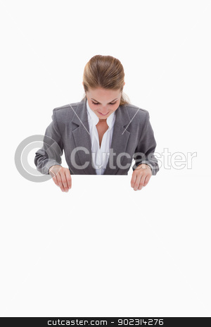 Bank employee looking down at blank sign in her hands stock photo, Bank employee looking down at blank sign in her hands against a white background by Wavebreak Media