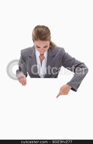 Bank employee pointing down at blank sign in her hands stock photo, Bank employee pointing down at blank sign in her hands against a white background by Wavebreak Media