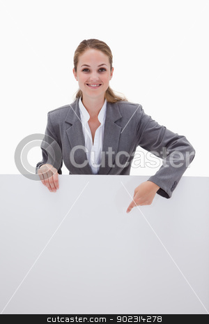 Smiling bank employee pointing down at blank sign stock photo, Smiling bank employee pointing down at blank sign against a white background by Wavebreak Media