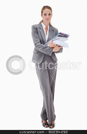 Office employee with pile of paperwork stock photo, Office employee with pile of paperwork against a white background by Wavebreak Media