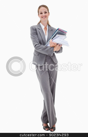 Smiling office employee with pile of paperwork stock photo, Smiling office employee with pile of paperwork against a white background by Wavebreak Media
