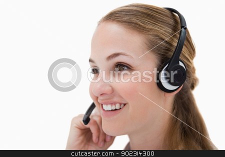 Side view of smiling call center agent  stock photo, Side view of smiling call center agent against a white background by Wavebreak Media