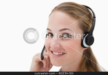 Side view of smiling call center agent with headset stock photo, Side view of smiling call center agent with headset against a white background by Wavebreak Media