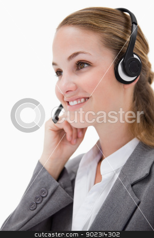 Side view of listening call center agent with headset on stock photo, Side view of listening call center agent with headset on against a white background by Wavebreak Media