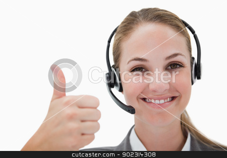 Smiling call center agent giving thumb up stock photo, Smiling call center agent giving thumb up against a white background by Wavebreak Media