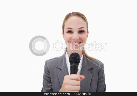 Smiling woman with microphone stock photo, Smiling woman with microphone against a white background by Wavebreak Media