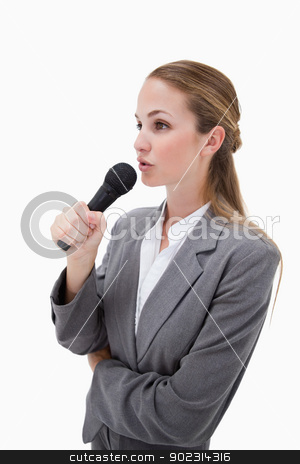 Side view of woman with microphone stock photo, Side view of woman with microphone against a white background by Wavebreak Media