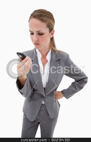 Irritated bank employee reading text message stock photo, Irritated bank employee reading text message against a white background by Wavebreak Media