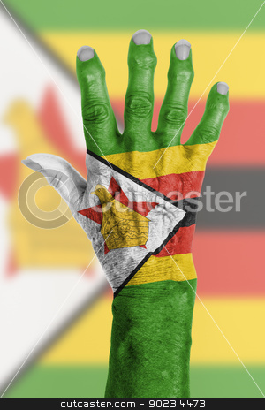 Hand of an old woman wrapped in flag stock photo, Hand of an old woman wrapped in flag of Zimbabwe by michaklootwijk