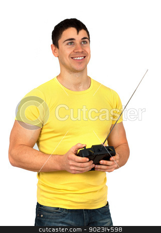 Man with radio remote control stock photo, Young athletic man holding a radio remote control (controlling handset) for helicopter or plane.Isolated on white background by borojoint