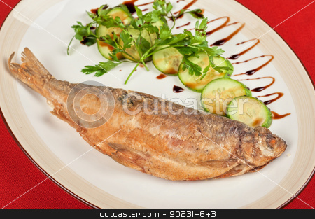 Fried peled fish stock photo, Fried peled fish with cucumbers and greens by olinchuk