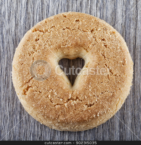 Biscuit stock photo, A biscuit with a hole in shape of heart in the center by Fabio Alcini