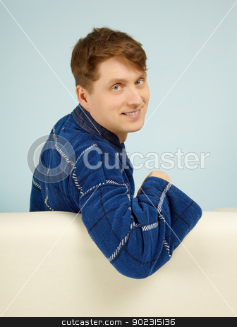 Happy smiling man sitting on couch in dressing gown stock photo, Happy smiling man sitting on a couch in his dressing gown on blue by Alexey Romanov