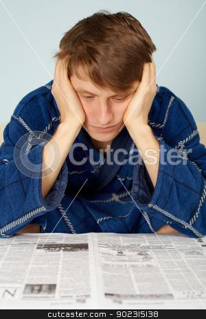 Sad man reading a newspaper stock photo, Sad man reading a newspaper at home in his dressing gown by Alexey Romanov