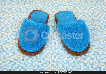 Pair of soft blue slippers stock photo, A pair of soft blue slippers on the floor by Alexey Romanov