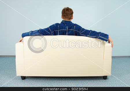 Young man sitting at home on couch stock photo, A young man is sitting comfortably at home on the couch by Alexey Romanov