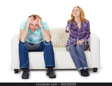 Nervous husband and wife sitting on couch watching TV stock photo, Nervous husband and wife sitting on the couch watching TV isolated on white background by Alexey Romanov