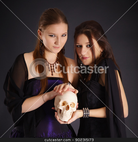 Two young girls with a human skull stock photo, Two young girls in the dark with a human skull by Alexey Romanov