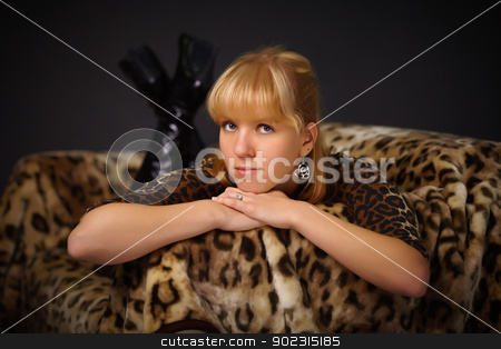 Young beautiful girl lying on sofa stock photo, Young beautiful girl lying on the sofa - Leopard theme on black background by Alexey Romanov