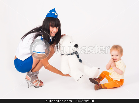 Attractive stewardess and baby girl stock photo, Pretty stewardess suggest bear toy to little baby girl by Aikon