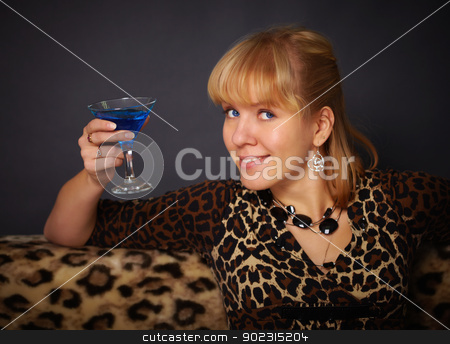Beautiful young woman drinking blue cocktail stock photo, Beautiful young woman drinking blue cocktail on black background by Alexey Romanov