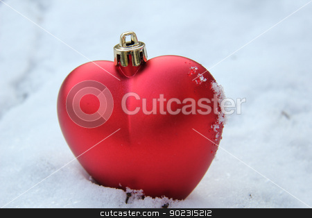 Heart shaped ornament in the snow stock photo, Red, heart shaped christmas ornament in fresh snow by Porto Sabbia
