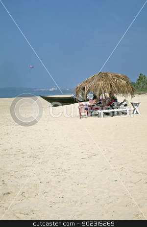 Holidaymakers under coconut huts on secluded be stock photo, Portrait of secluded beach close of a city with dayt rippers and holidaymakers under the shade of coconut parasols. White sand, blue sky, sea, surf, para glider and fishing boats for a backdrop. Generic tropical shot location, Goa India by Kantilal Patel