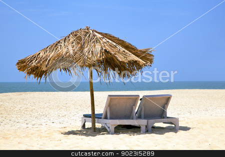 Watching Tv tropical Style stock photo, A generic tropical deserted beach with loungers under a coconut leaf parasol. Blue sky, ocean, gentle surf sound and clean sandy beach. Location, Goa India by Kantilal Patel