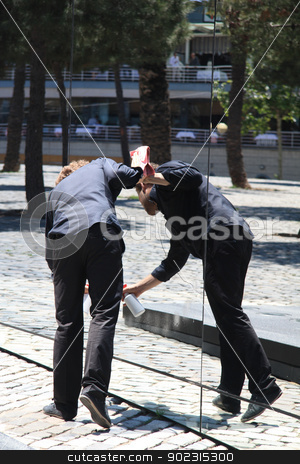 Man cleaning mirror stock photo, Man busy cleaning a giant mirror by Porto Sabbia