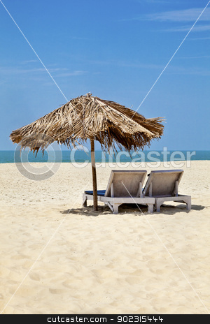 Vertical landscape sea sand beach loungers stock photo, A generic vertical portrait of a tropical deserted beach with loungers under a coconut leaf parasol. Blue sky, ocean, gentle surf sound and clean sandy beach. Location, Goa India by Kantilal Patel