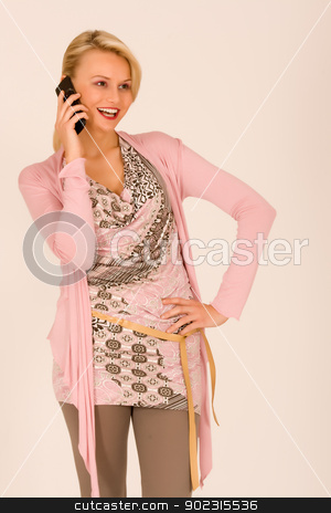 Woman at telephone stock photo, Woman at the phone with a mobile phone by Roland Stollner