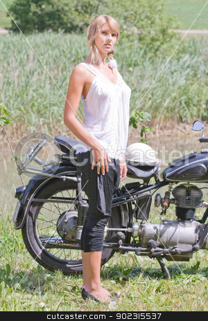 Young woman with bike stock photo, Fashionable young woman posing in front of a vintage Mottorad by Roland Stollner
