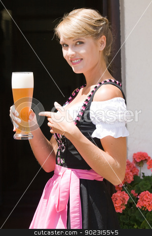 Young woman in dirndl with white beer stock photo, Young Bavarian operation served a glass of white beer by Roland Stollner
