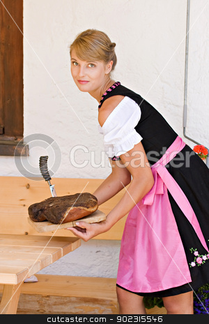 Bavarian woman in a dirndl stock photo, Bavarian Dirndl woman serving a bacon on a plate Alm by Roland Stollner