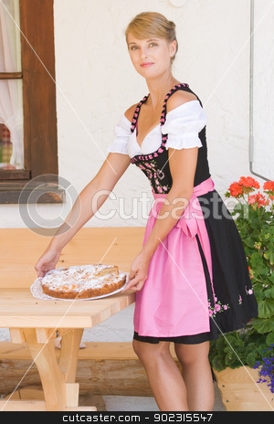Young woman in dirndl with cake stock photo, Young Bavarian operation served a cake by Roland Stollner