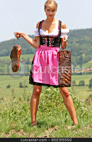 Young woman in dirndl with bacon stock photo, Young Bavarian girl with fresh bacon on the meadow by Roland Stollner