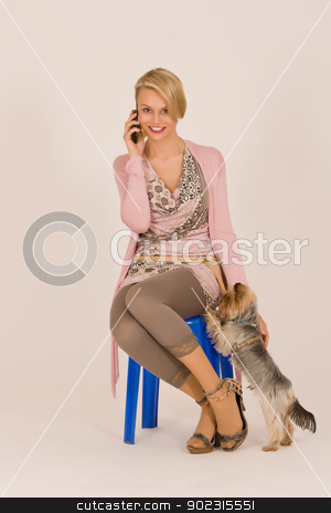 Woman with dog stock photo, Young woman phoning with a cell phone with the dog by Roland Stollner