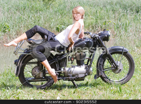 Young woman on motorcycle stock photo, Fashionably dressed woman seated on an old motorcycle by Roland Stollner