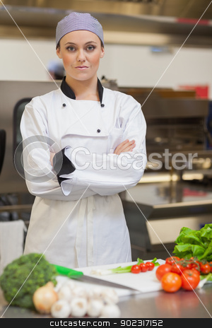 Chef standing beside chopping board and vegetables stock photo, Serious chef standing beside chopping board and vegetables in the kitchen by Wavebreak Media