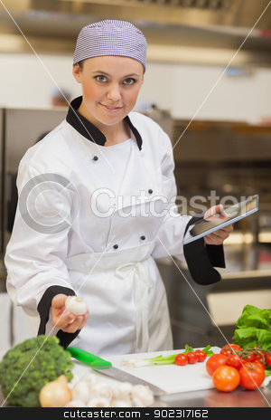 Chef holding digital tablet and mushroom  stock photo, Chef smiling and holding digital tablet and mushroom in the kitchen by Wavebreak Media