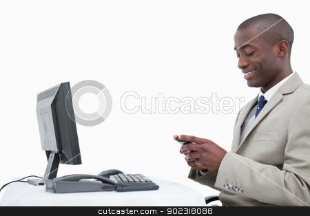 Side view of a smiling businessman sending a text message stock photo, Side view of a smiling businessman sending a text message against a white background by Wavebreak Media