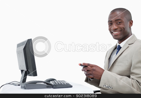 Smiling businessman sending a text message stock photo, Smiling businessman sending a text message against a white background by Wavebreak Media