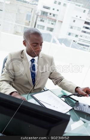 Portrait of a businessman hanging up stock photo, Portrait of a businessman hanging up in his office by Wavebreak Media