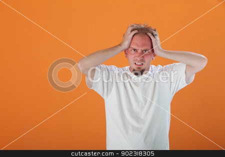 Man Holding His Head stock photo, Caucasian man holding his head in pain or anger  by Scott Griessel