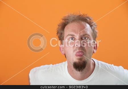 Man Sticks Out His Tongue stock photo, Bearded Caucasian man on orange background sticks out his tongue by Scott Griessel