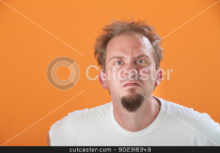 Pissed-off Man stock photo, Frowning bearded Caucasian man on orange background by Scott Griessel