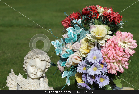 Angle statue and flower bouquet stock photo, Angle statue in cemetery next to bouquet of flowers. Grass in background with copy space. by Martin Crowdy
